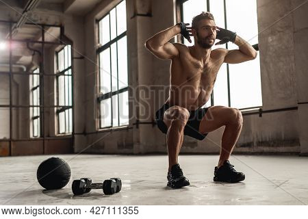 Low Angle Full Body Of Strong Bearded Shirtless Male Squatting While Exercising In Spacious Gym With