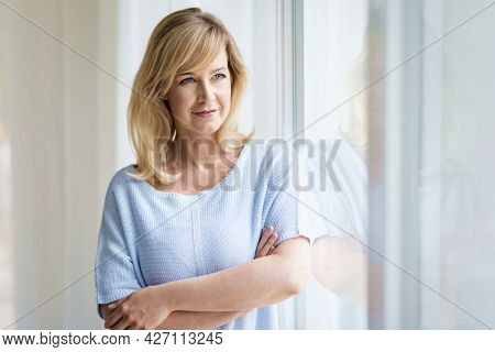Portrait Of Beautiful Blond Haired Woman Standing At The Window And Daydreaming.