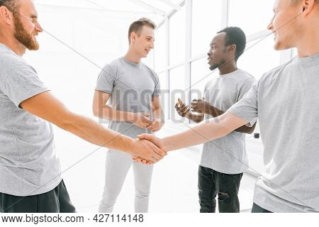 Welcome Handshake Of Friends In A Bright Office.