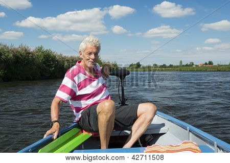 Elderly man in boat at the river poster