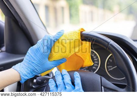 Female Hands With Blue Gloves Wiping Car Steering Wheel With Disinfectant Wipe.