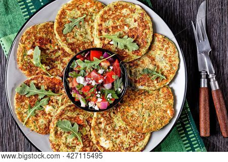 Zucchini Fritters With Dill Served With Fresh Feta Cheese Tomato Salad On A Plate On A Wooden Table,