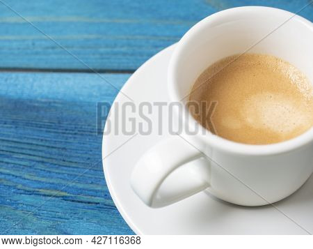 A White Coffee Mug With A Full Espresso Is Set On A Saucer And On A Blue Wooden Background. Coffee,