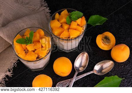 Apricot Yogurt With Muesli In A Glass On A Black Background. View From Above.