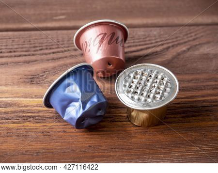 Several Used Aluminum Capsules For The Coffee Machine Lie On A Brown Wooden Background. Concept Of R
