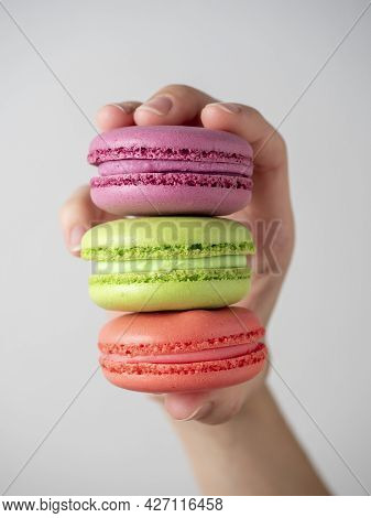 Close-up Of A Woman's Hand Holding Three Multi-colored Macaroons. Front View, Vertical Photo