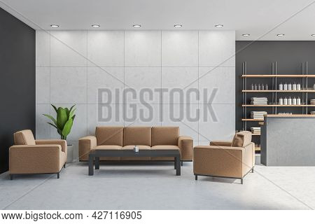 Reception Zone With Light Brown Sofa, Armchairs And Black Coffee Table. Dark Grey Walls With Light T