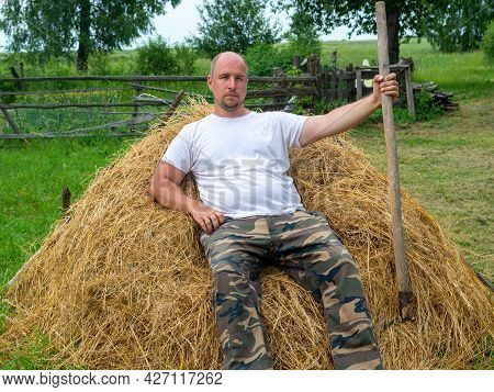 A Middle-aged Man Dressed In Trousers And A T-shirt Is Sitting On A Stack Of Yellow Hay And Holding