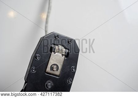 Swage For Network Telecommunication Rj45 Cables On A White Surface. A Cable Is Inserted Into The Too