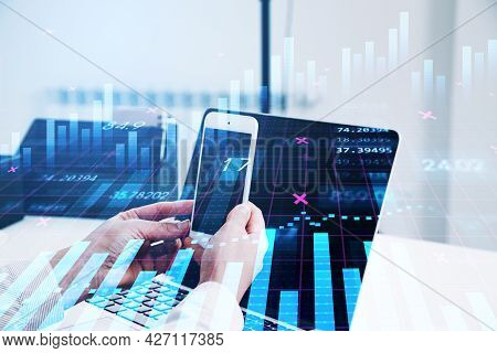 Businessman Or Stock Trader Analyzing Stock Graph Chart Using Smartphone With Touchscreen And Laptop