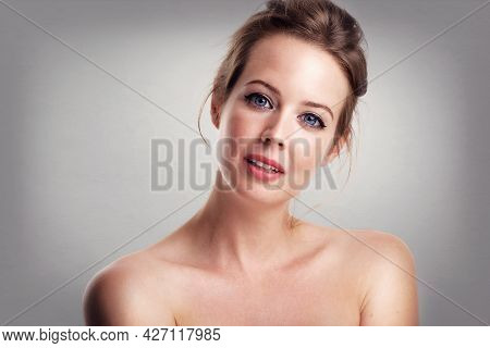 Close-up Beauty Portrait Of Gorgeous Woman Wearing Perfect Makeup While Standing At Grey Isolated Ba