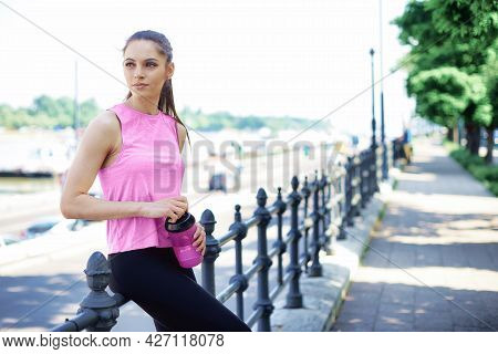 Shot Of Young Woman Holding A Shaker In Her Hand While Relaxing After Running In The City.