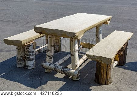 A Bench And A Table Made Of Wood In A Street Cafe