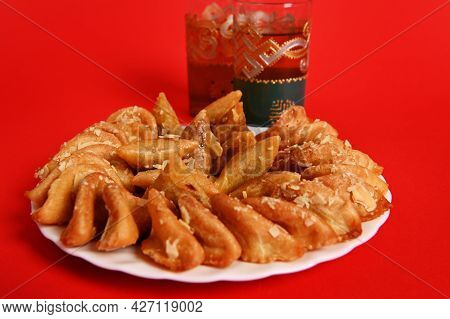 A Plate With Arabian Dessert From Almond Flour And Honey And Two Beautiful Glass With Traditional Mo