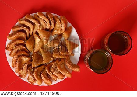 Flat Composition With Oriental Moroccan Dessert On Plate Next To Two Glasses In Arabic Style On Red