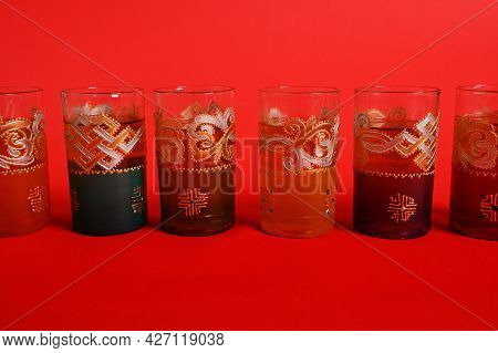 Multicolored Glasses For Moroccan Green Mint Tea, Decorated In Oriental Style. Isolated On Red Backg