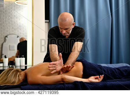 Middle Aged Masseur Performing Professional Back Massage Of Client Lying On Massage Couch In Massage
