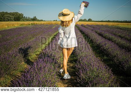 Happy Woman Sitting In Lavender Field In Summer Morning.