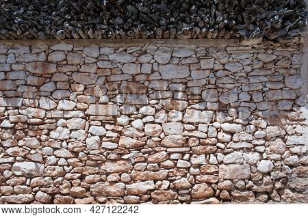 Ancient Traditional Wall Of Stone With Wood Sticks On Top Of It. Texture, Background