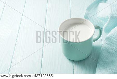 Blue Mug Of Fresh Milk On A Wooden Table. Fresh Milk On A Blue Background