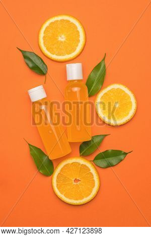 Two Bottles Of Orange Juice, Leaves And Pieces Of Orange On An Orange Background. The Concept Of The