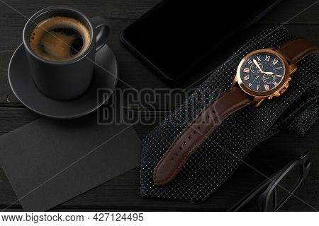 Men's Wrist Watch On A Black Tie, A Hot Cup Of Coffee And A Smartphone On A Wooden Table. Black Enve