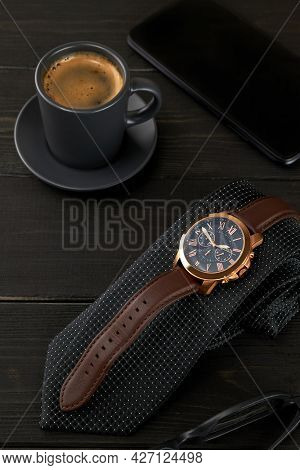 Men's Wrist Watch On A Black Tie Next To A Cup Of Hot Coffee And A Smartphone On A Wooden Table