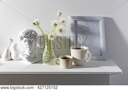 A Bunch Of Fluffy Dandelions In A Chemical Flask, An Empty Photo Frame, A Cup Of Espresso Coffee, An