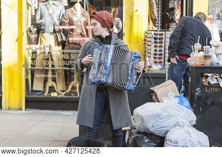 London, Uk - November 2019, Girl Playing The Accordion Against The Background Of A Heap Of Rubbish