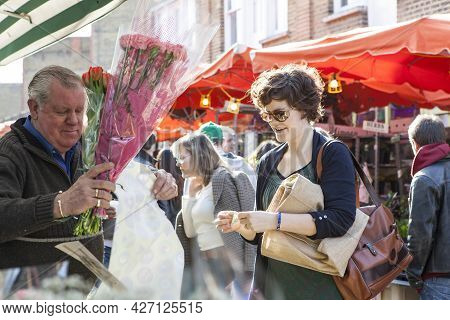 London, England - October 12, 2018 People Buying Flowers At Columbia Road Flower Market. This London