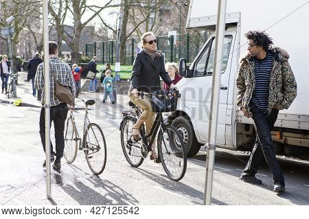 London, Uk - September 2019, People With Bicycles. A Woman On A Bicycle Catches Up With A Man In A S