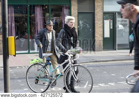 London, Uk - September 2019, People With Bicycles, Short-haired Blonde Girl With A Bicycle And An El