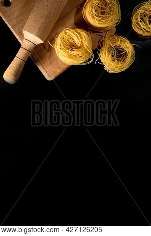 Rolled Tagliatelle Shape Of Italian Pasta On Black Stone Background . High Quality Photo