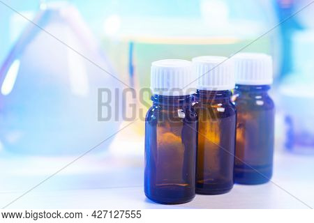 Three Bottles With Chemicals On A Blurred Background. Pharmaceutical Industry. Health Care And Medic