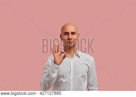 Ok Sign, Quality Symbol. Serious Bald Guy With Bristle In White Shirt Showing Okay Gesture, Confirms