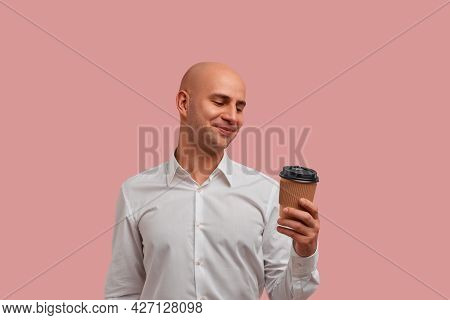Photo Of Relaxed Satisfied Bald Guy In White Shirt, Holds Paper Cup Of Coffee And Looks At Beverage
