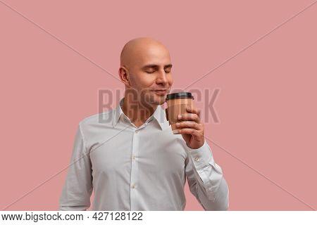Enjoy Drinking Caffeine Beverage. Attractive Bald Man With Bristle, Smells Aromatic Coffee, Has Brea