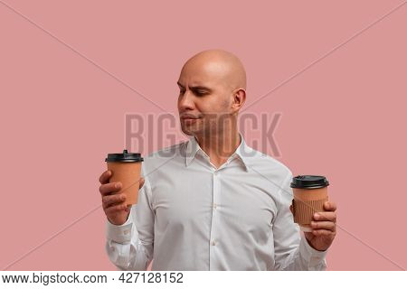 What To Choose. Thoughtful Bald Man With Bristle, Holds Two Paper Cups With Beverages, Trying To Sel