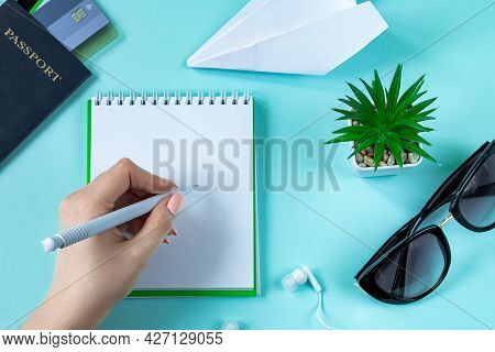 A Woman Is Planning A Summer Vacation. Travel Accessories On A Blue Background. Passport, Sun Glasse