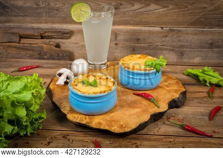 Pots With Mushroom Julienne On A Wooden Board, Decorated With Herbs. Julienne In Cocotte With Yellow