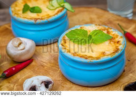 A Pot Of Mushroom Julienne On A Wooden Board, Decorated With Herbs. Julienne In Cocotte With Yellow