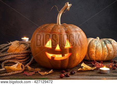 A Glowing Pumpkin Lantern, Jack's Head On A Background Of Foliage, Berries And Candles. A Halloween