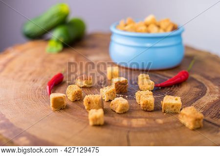 Square-shaped Breadcrumbs In A Pot. Oven-fried Golden Brown Bread Crumbs. Cucumbers And Chili Pepper