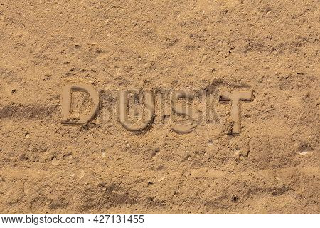 The Word Dust Embossed On Dusty Road Surface In Flat Lay Perspective