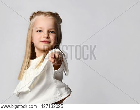 Close Up Of The Index Finger Of A Cute Little Girl Pointing At You. Blonde Posing On A White Backgro