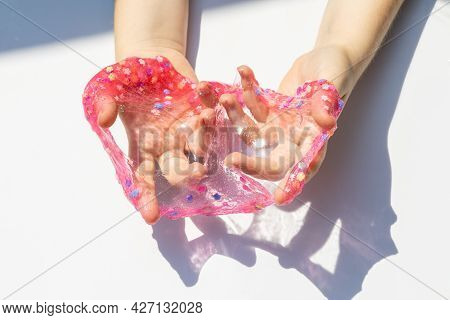 Texture Of Decorated Shiny Transparent Slime, Baby Hands With Slime Close Up
