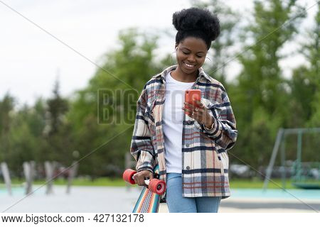 Happy Urban Afro American Girl Texting Hold Smartphone. Casual Longboarder Female Cheerful With Long