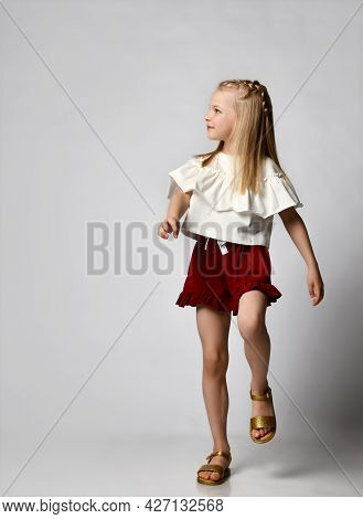 Cute Smiling Little Girl In A White Blouse With Flounces, Burgundy Shorts And Sandals, Walks Briskly