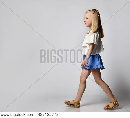 Cute Smiling Little Girl In A White Blouse With Flounces, Blue Shorts And Sandals, Walks Briskly And