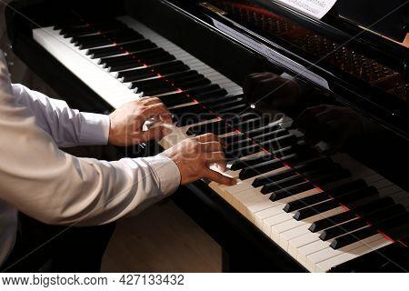 Man Playing Piano Indoors, Closeup. Talented Musician
